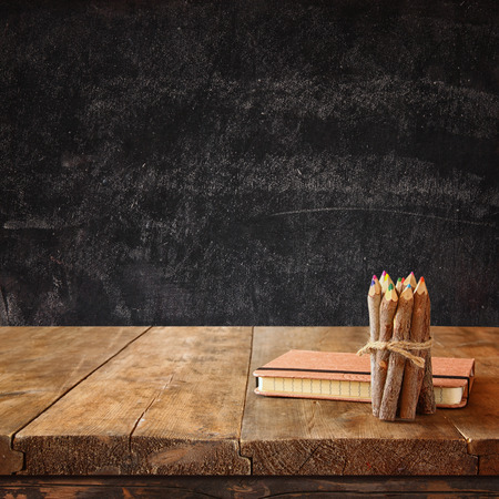 notebook: vintage notebook and stack of wooden colorful pencils on wooden textures table against chalkboard background