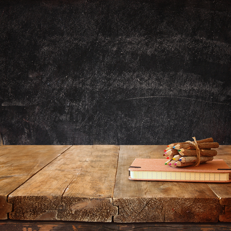 notebooks: vintage notebook and stack of wooden colorful pencils on wooden textures table against chalkboard background