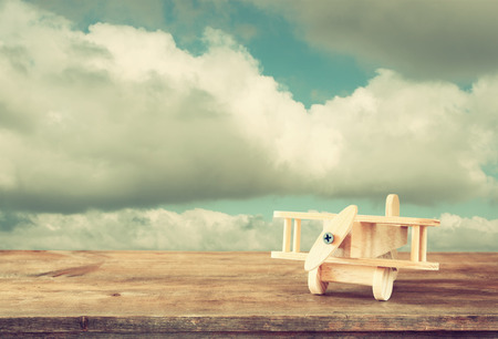 airplane: image of wooden toy airplane over wooden table against cloudy sky. retro style image Stock Photo
