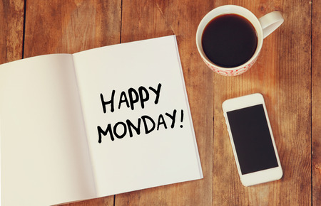 notebook with the phrase happy monday written on it, coffee cup and amart phone. filtered image. Foto de archivo
