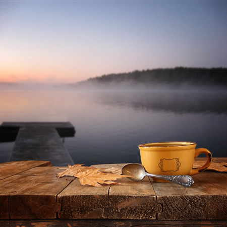 pier: front image of coffee cup over wooden table in front of calm foggy lake view at sunset