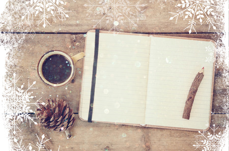 overly: top image of open notebook with blank pages, next to pine cones and cup of coffee over wooden table. top image, glitter overly with snowflakes Stock Photo