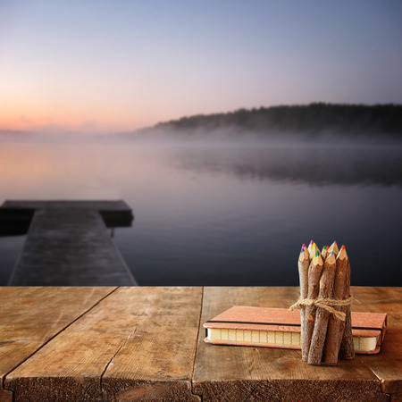 notebooks: vintage notebook and stack of wooden colorful pencils on wooden texture table in front of calm foggy lake view at sunset