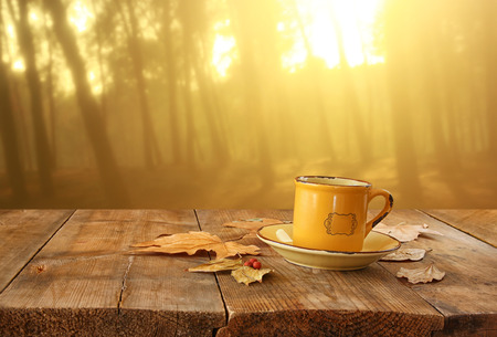 coffee tree: front image of coffee cup over wooden table and autumn leaves in front of autumnal sunset background