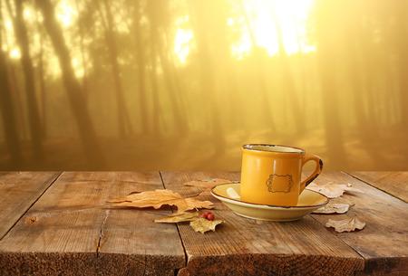 otoñales: imagen delante de la taza de café sobre la mesa de madera y hojas de otoño de fondo puesta de sol otoñal