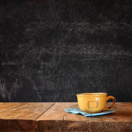 room for text: front image of coffee cup over wooden table and autumn leaves in front and blackboard background with room for text Stock Photo