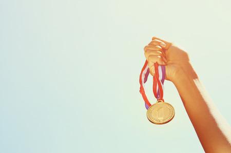 donna mano alzata, tenendo medaglia d'oro contro il cielo Archivio Fotografico