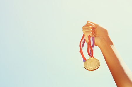 woman hand raised, holding gold medal against sky