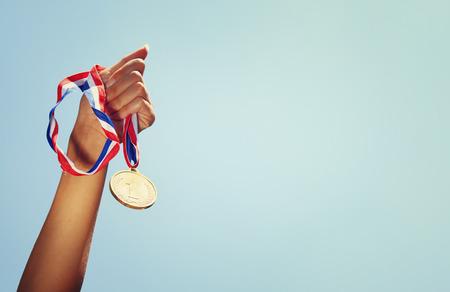 oro: levant� la mano de mujer, la celebraci�n de la medalla de oro contra el cielo Foto de archivo