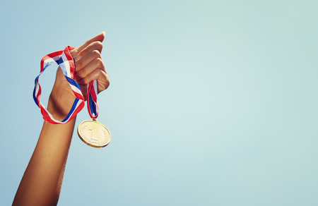 achieve goal: woman hand raised, holding gold medal against sky