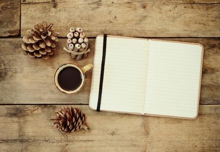 top beeld van open notebook met blanco pagina's, naast de dennenappels en kopje koffie over houten tafel.