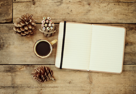 writing table: top image of open notebook with blank pages, next to pine cones and cup of coffee over wooden table. Stock Photo