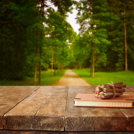 vintage notebook and stack of wooden colorful pencils on wooden texture table in front of countryside forest view
