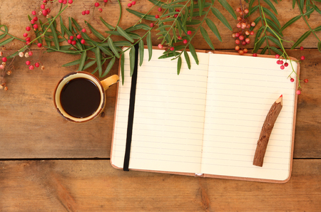 tip of the leaf: open blank vintage notebook and wooden pencil over wooden table next to coffee cup . ready for adding text. retro filtered image