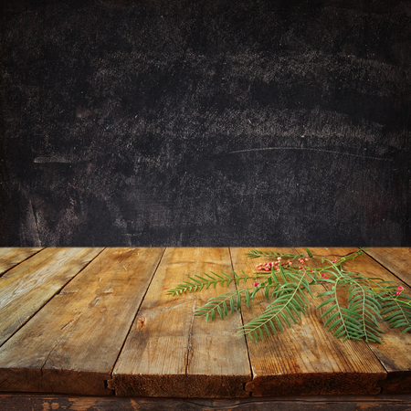 vintage photo: front image of wooden table and autumn leaves in front and blackboard background with room for text Stock Photo