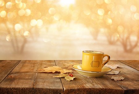 forest tea: front image of coffee cup over wooden table and autumn leaves in front of autumnal sunset background