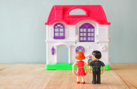 soñando: concepto de imagen de la joven pareja en frente de la nueva casa. poco plástico muñecas de juguete masculino y femenino, foco selectivo.