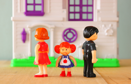 conflicts: concept image of parent busy or angry and child in the middle in front of. little plastic toy dolls male, female, child, selective focus. Stock Photo