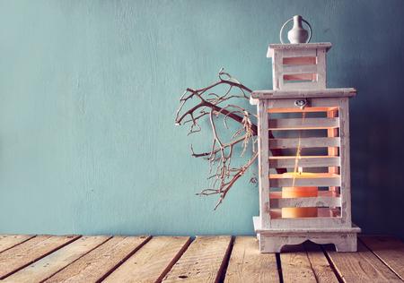 candela: basso chiave immagine di legno bianco lanterna d'epoca con la candela accesa e rami di albero su tavola di legno. immagine filtrata retrò