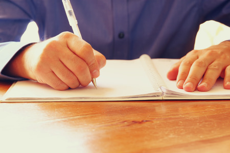 writing desk: close up image of male hands writing at notebook. selective focus. Stock Photo
