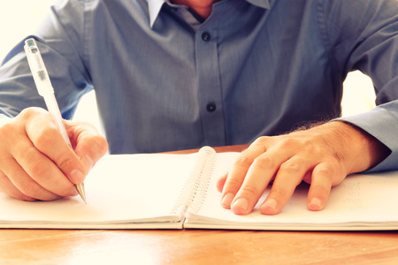 close up image of male hands writing at notebook. selective focus. Reklamní fotografie