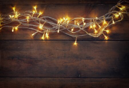 feliz navidad: Christmas warm gold garland lights on wooden rustic background. filtered image Stock Photo