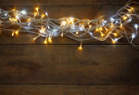 christmas garland: Christmas warm gold garland lights on wooden rustic background. filtered image Stock Photo
