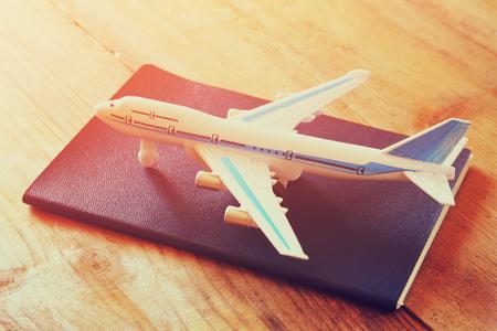 おもちゃの飛行機と木製のテーブルの上のパスポート。レトロなスタイルのイメージ