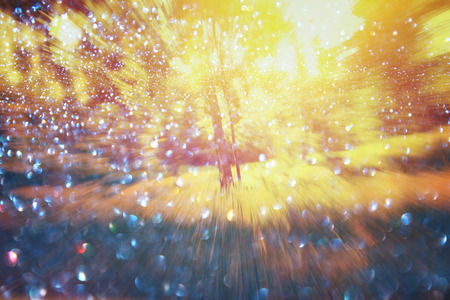 abstract photo of light burst among trees and glitter bokeh lights. blurred and filtered