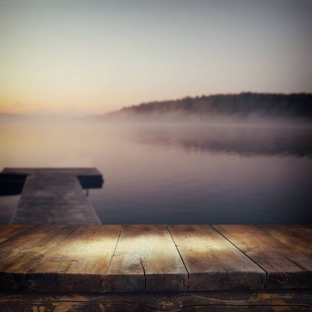 mistery: vintage wooden board table in front of abstract photo of misty and foggy lake at morning sunrise. Stock Photo
