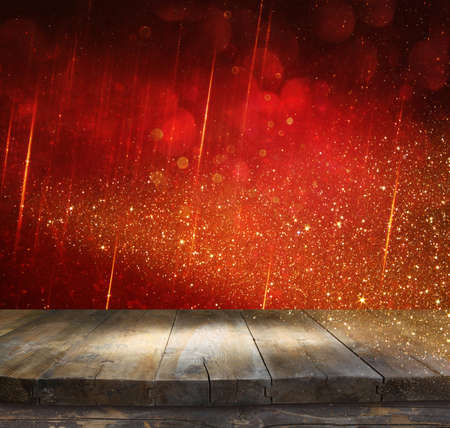empty table: rustic wood table in front of glitter red and gild bokeh lights