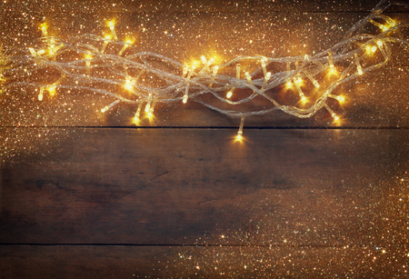 feliz navidad: Christmas warm gold garland lights on wooden rustic background. filtered image with glitter overlay Stock Photo