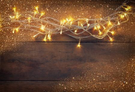 Weihnachten warmes Gold Kranz leuchtet auf hölzernen rustikalen Hintergrund. gefilterte Bild mit Glitzer-Overlay Standard-Bild - 45367858