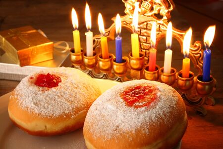 chanukiah: image of jewish holiday Hanukkah with menorah traditional Candelabra, donuts and wooden dreidels spinning top. retro filtered image