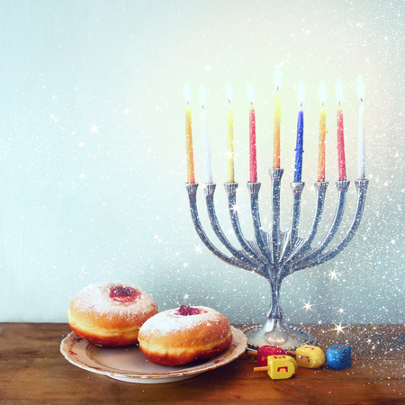 chanukah: image of jewish holiday Hanukkah with menorah traditional Candelabra, donuts and wooden dreidels spinning top. retro filtered image with glitter overlay
