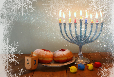 image of jewish holiday Hanukkah with menorah traditional Candelabra, donuts and wooden dreidels spinning top. retro filtered image with glitter and snowflakes overlay
