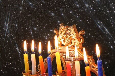 hanukka: Image of jewish holiday Hanukkah background with menorah traditional candelabra Burning candles over black background