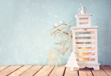 white wooden vintage lantern with burning candle and tree branches on wooden table. retro filtered image with glitter overlay Stock Photo