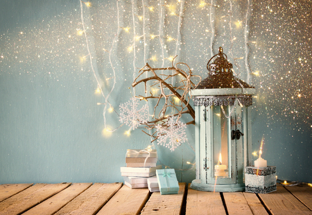 white wooden vintage lantern with burning candle christmas gifts and tree branches on wooden table. retro filtered image with glitter overlay