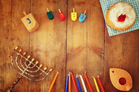 jewish background: top view image of jewish holiday Hanukkah with menorah traditional Candelabra, donuts and wooden dreidels spinning top. retro filtered image Stock Photo
