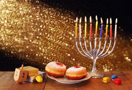 simbolos religiosos: bajo clave de imagen de día de fiesta judío Jánuca con el menorah, donas y dreidels de madera que hacen girar la parte superior. retro imagen filtrada