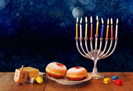 low key image of jewish holiday Hanukkah with menorah, doughnuts and wooden dreidels spinning top. retro filtered image Zdjęcie Seryjne