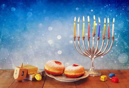 low key image of jewish holiday Hanukkah with menorah, doughnuts and wooden dreidels spinning top. retro filtered image Stock Photo