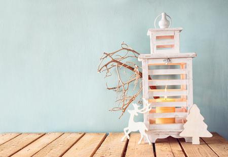 velas de navidad: blanco linterna de la vendimia de madera con velas encendidas, ciervos de madera, regalos de Navidad y ramas de los árboles en la mesa de madera. retro imagen filtrada