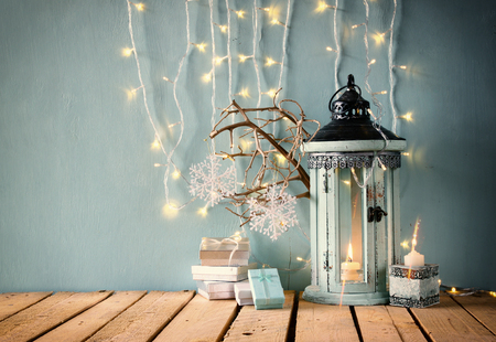 christmas candle: low key image of white wooden vintage lantern with burning candle christmas gifts and tree branches on wooden table. retro filtered image Stock Photo