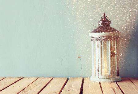 witte houten uitstekende lantaarn met brandende kaars en boomtakken op houten tafel. retro gefilterde afbeelding met glitter overlay