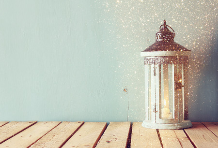 white wooden vintage lantern with burning candle and tree branches on wooden table. retro filtered image with glitter overlay Stockfoto