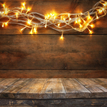 feliz navidad: wood board table in front of Christmas warm gold garland lights on wooden rustic background. filtered image. selective focus