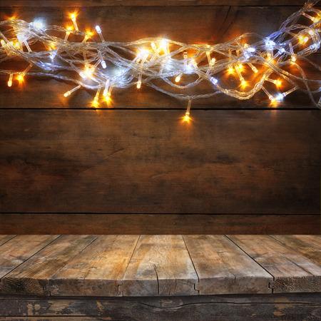 tablero: mesa de tablero de madera en frente de Navidad luces cálida guirnalda de oro sobre fondo de madera rústica. filtrada imagen. enfoque selectivo Foto de archivo