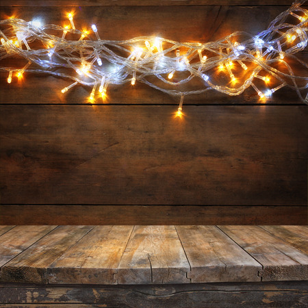 navidad navidad: wood board table in front of Christmas warm gold garland lights on wooden rustic background. filtered image. selective focus
